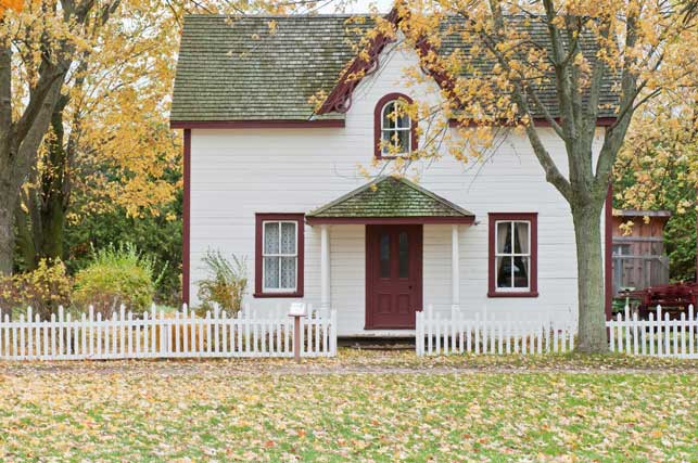 A house with a white picket fence in fall