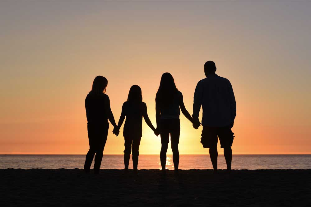 A family silhouette at the beach holding hands